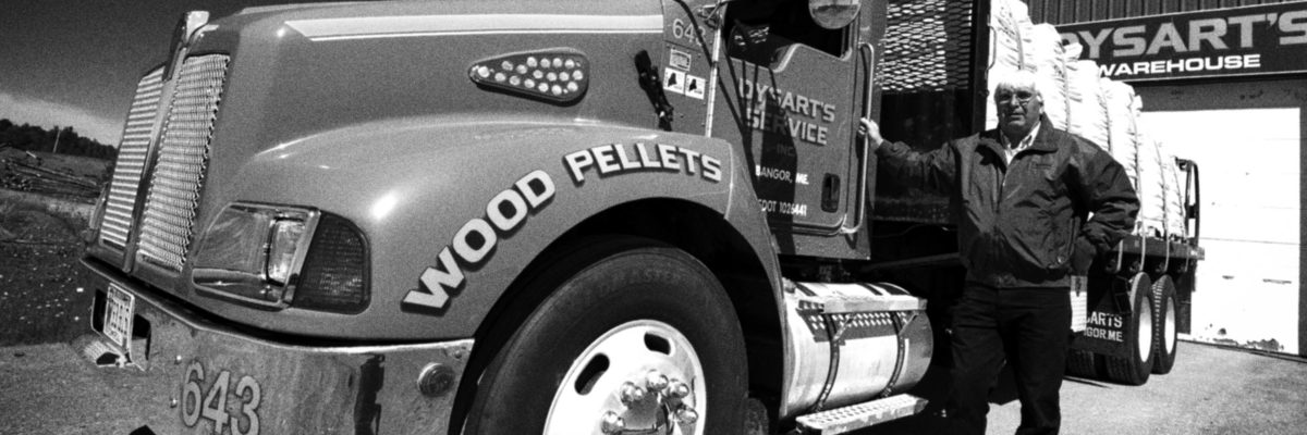 black and white photo of man standing next to dysart's service wood pellets truck